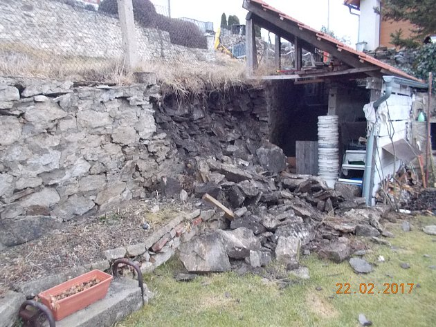 Opěrná zeď se vyvalila na pozemek rodinného domu. Nad ní je cesta, která je nyní staticky ohrožena.
