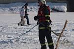 Předtím, než hasiči vytáhli na břeh jezera potopený automobil, museli vyčistit led od sněhu a v ledu vyříznout pás od místa, kde se vůz probořil do vody, až ke břehu.
