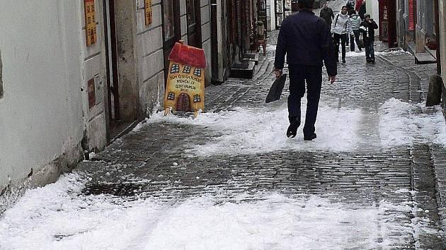 Úzké uličky Českého Krumlova se při sesouvání sněhu ze střech mění v pasti, kde není kam se ukrýt. V neděli kolem 22. hodiny začalo v regionu pršet a při ranním mrazíku se voda změnila v ledovku.