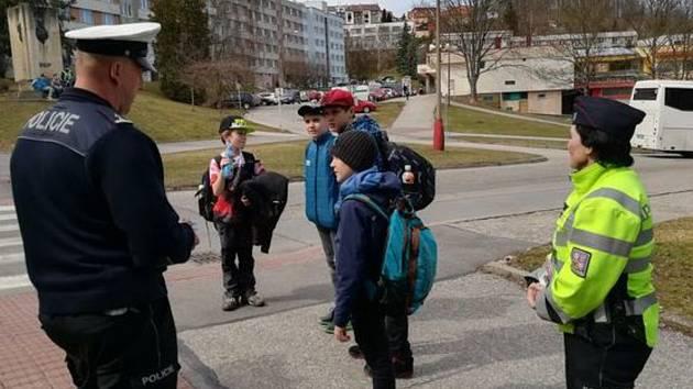Policisté na frekventovaných přechodech učí děti, jak se chovat v silničním provozu.