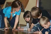 Při nocování v hornoplánské knihovně se děti ani na chvilku nenudily. Kvízy s pohádkovou tématikou (na snímku luštění křížovky, jejíž tajenkou byla část básně Františka Hrubína) střídaly hry zaměřené na procvičení motoriky.