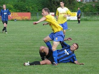 Nesmlouvavost derby dokumentuje i souboj autora vyrovnávací branky hostů Michala Chromého (v popředí), po jehož ataku se na trávníku ocitl chvalšinský Tomáš Holas.