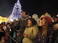 Koledy si na českokrumlovské náměstí Svornosti přišla zazpívat asi stovka lidí všeho věku.