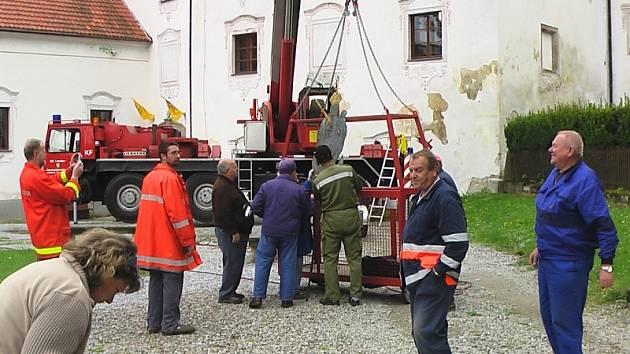Madonu sundali ze střechy kaple  sv. Anny Hřbitovní  vyšebrodští a rakouští hasiči s pomocí  ramene speciálního jeřábu  s klecí.