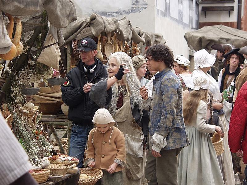 Na podobě scény, natáčené  v českokrumlovské ulici Parkán, se režisér pohádky Tři životy Jiří Strach (vlevo) v září roku 2007 domlouval s herečkou Gabrielou Vránovou. Ta se zhostila role kořenářky.