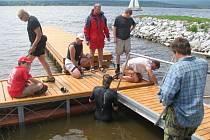 Českokrumlovští vodní záchranáři opět zahájili neustálou službu u lipenského jezera. V sobotu na jezeře u své základny v Dolní Vltavici usazovali novou lávku k novému molu.