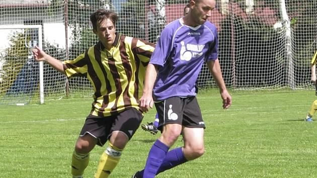 Výhru kájovského lídra přeboru v Holubově pečetil třetím gólem Jiří Čermák (u míče, v souboji s Matyášem Buštou).