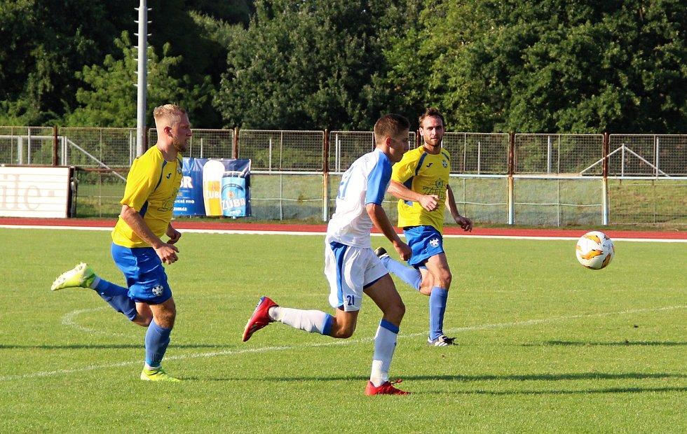 Úvodní kolo divize E nabídlo derby v Přerově mezi domácí Viktorkou (v bílém) a Kozlovicemi. Petr Mirvald před gólovou střelou na 1:0.