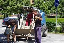 Dělníci usazují reliéfní pás ze zámkové dlažby, který oddělí chodník od cyklodopravy