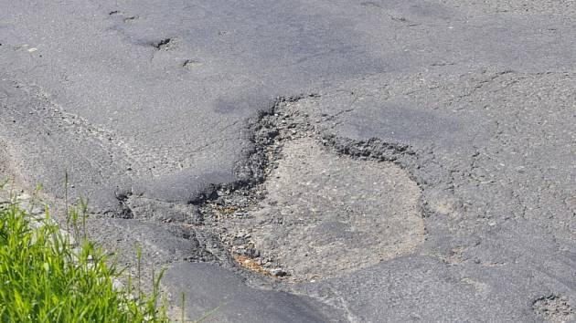 Některé díry na silnicích v Přerově jsou přímo ukázkové. Podle obyvatel města už ale ohrožují bezpečnost řidičů (na snímku výtluky v ulici u Penny marketu nedaleko hřbitova)