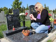 Matka nejmladší oběti metanolové kauzy na Přerovsku Jana Švejdová zapaluje svíčku na hrobě své dcery Michaely. Zemřela loni desátého září v ubytovně v Oseku nad Bečvou poté, co se napila závadného alkoholu.