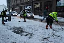 Pracovníci technických služeb odhrnují sníh na přechodu pro chodce u velké pasáže.