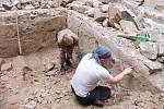 Bádání archeologů během rekonstrukce renesančního paláce na Helfštýně. Členové archeologického týmu studují relikty heraldické výzdoby na nejstarší omítce místnosti.