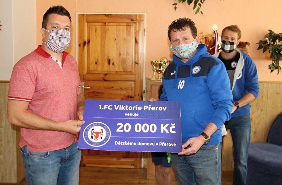 Fotbalisté 1. FC Viktorie Přerov pomáhají potřebným. Předseda klubu Břetislav Holouš (vpravo) předává šek řediteli Dětského domu Přerov Luďku Doleželovi.