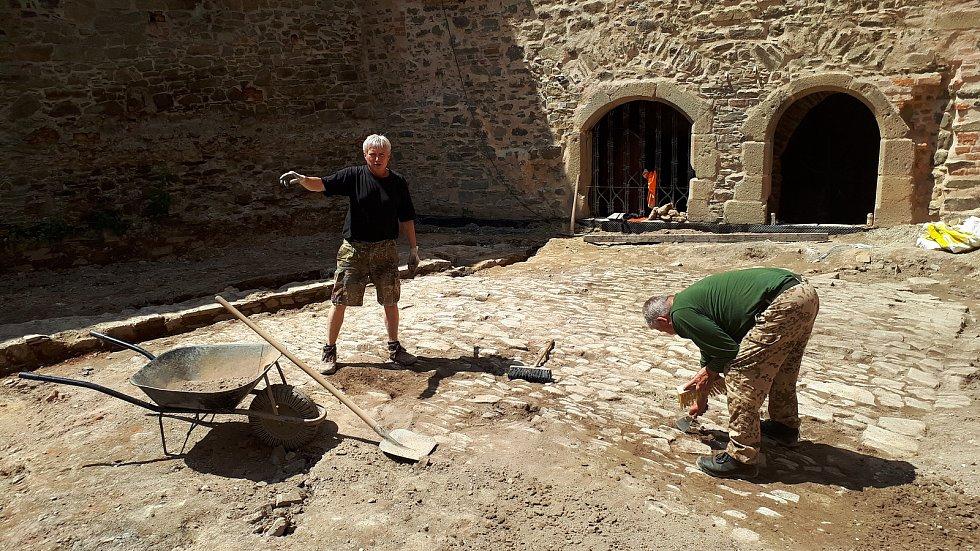 Členové archeologického týmu Jan Novotný a Josef Dokoupil preparují povrch renesanční dlažby na Helfštýně