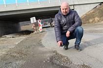 Silnice ve Vinarech u Přerova je poničená stavbou dálnice D1 Lipník - Přerov. (Na snímku ukazuje díry na cestě předseda výboru místní části Vladimír Machura).