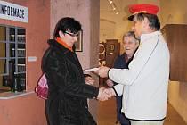 Pokladník Ota Bujnoch předává pětisté návštěvnici výstavy Pavle Kubanové penežní kupón