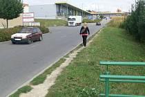 Chodník na Družstevní ulici mezi obchodními středisky lidem schází. Vyšlapali si pěšinu podél silnice.