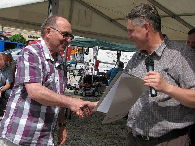 Karel Fojtík (vlevo) přebírá certifikační známku Moravská brána regionální produkt na farmářských trzích v Hranicích.