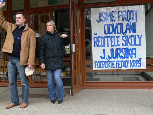 Na budově školy visí plakát proti rozhodnutí radních.