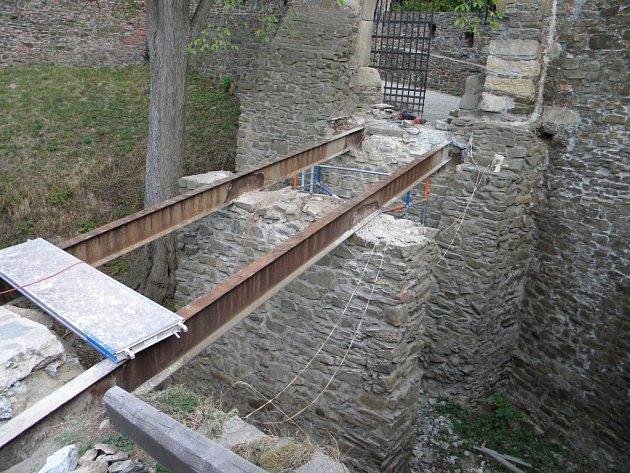 Obnažený prostor před třetí bránou po stržení dřevěných konstrukcí s pohledem na prorezlé ocelové nosníky.