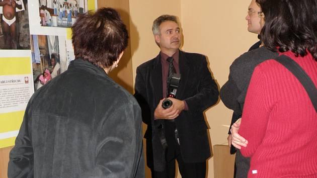 Výstava, kterou zahájil ředitel olomoucké charity Václav Keprt (na snímku s fotoaparátem), má lidem přiblížit, jak se žije v místech, kde charita působí. níku