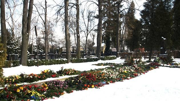 Květiny a věnce lemují stezku za obřadní síní přerovského městského hřbitova.