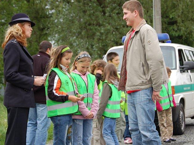 Děti z domaželické základní školy pod dohledem přerovské policejní mluvčí Miluše Zajícové udělovaly řidičům obrázky s veselým nebo zamračeným autem.