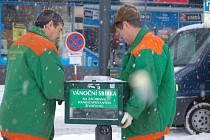 Pracovníci technických služeb odnášejí kasičku, do které lidé v době před Vánocemi vhazovali milodary. Výtěžek je tentokrát určen na záchrannou stanici pro handicapované živočichy.