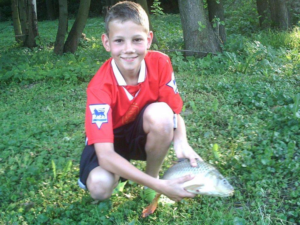 Tak tohle je první kapr chycený v soukromém rybníku pana Radka Škrobánka. Chytl ho jeho syn Hynek v pátek 3. července.