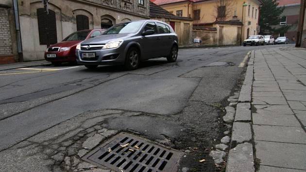 Rozbitá, záplatovaná silnice, tak to dnes vypadá v hranické Farní ulici. Tu brzy čeká oprava.
