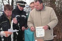 Strážci pořádku a policisté se probírají odpadem na černé skládce, kterou objevili  v biokoridoru Hloučela. Nalezené písemnosti je přivedly k pachatelce.