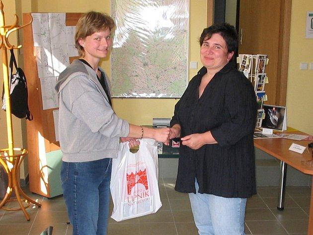 Průvodkyně předává Šárka Jadrníčková jubilejní návštěvnici drobné dárky.