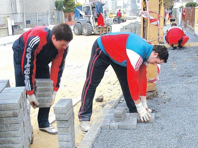 Stavebníci v Nerudově ulici v Přerově upravují povrch vozovky a dláždí chodníky
