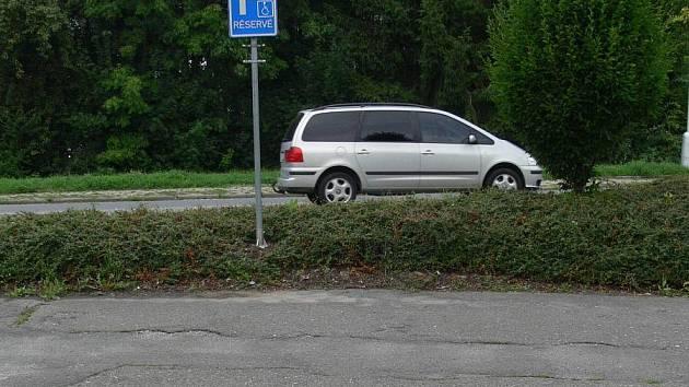 Asfaltová plocha před gymnáziem sloužící jako parkoviště