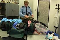 Vedoucí hranických policistů Petr Čech při zkoumání zloději ukradených věcí. Ilustrační foto