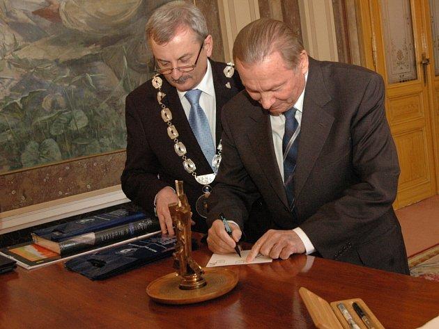 Exprezident podepisuje drobný dárek pro hradišťského místostarostu Evžena Uhra.