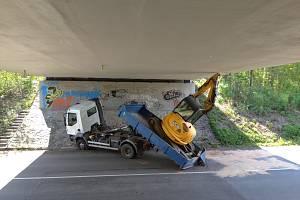 Bagr na korbě náklaďáku uvízl pod mostem