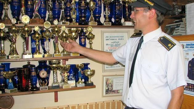 Starosta mistřických hasičů Matin Schön pyšně ukazuje bohatou sbírku pohárů, kterou mistřičtí vybojovali na různých soutěžích v požárním útoku.