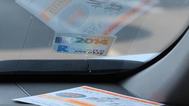 Parkovací karta a dálniční známka. Ilustrační foto.