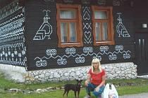 V Čičmanech u dřevěného domku s bílými ornamenty.