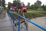 Hasiči odstraňují kusy stromů unášené vodou, které se zachytily pod mosty.PProfesionální hasiči z Uherského Hradiště, kteří v místní části Míkovice odstraňují pod mostem zaseklé kmeny stromů.