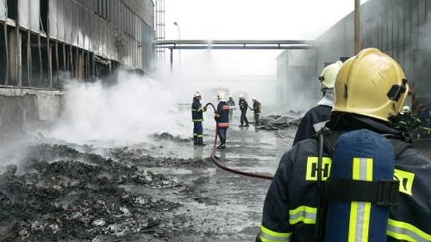 Hasiči likvidují požár podniku v Hluku.