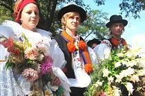 S dožínkovým věncem. Účastníci pouti byli oblečeni do tradičních krojů. Nechyběl ani symbol dožínek, věnec s obilím.
