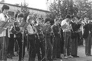 Mladí hudebníci Dolněmčanky vystupují v polovině 80. let minulého století spolu s ostřílenou částí kapely při jednom z prvomájových průvodů před sušičkou JZD Javořina.