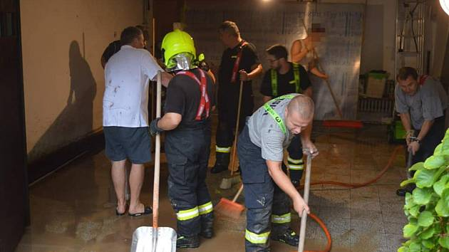 Členové SDH Kudlovice při úklidu suterénu v jednom z Kudlovických domů v pondělí 26. srpna.