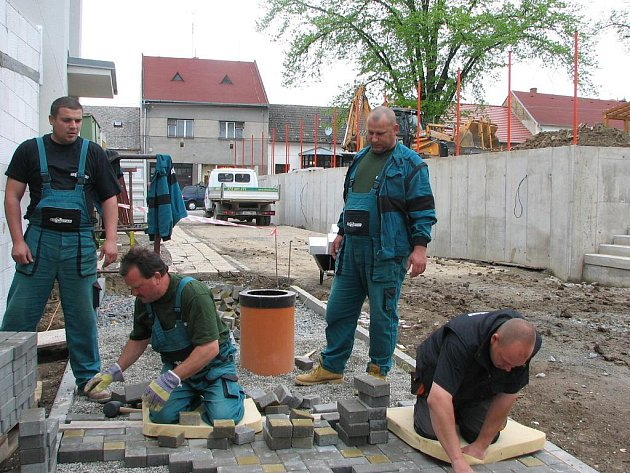 Při budování chodníků v Orlovně se díky dešti nepráší.