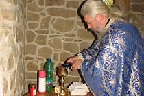 Kněz Kliment si připravuje před liturgií víno do kalichu a smíchá je s vodou.