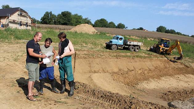 Starosta Modré Miroslav Kovářík vysvětluje pracovníkům dodavatelské firmy postup při budování rybníčku.