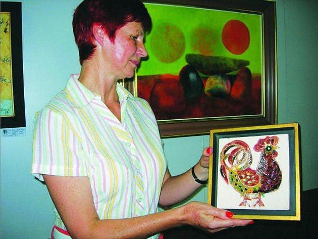 Galeristka Dana Slanicayová ukazuje kachel, který autor vytvořil v UHerském Hradišti.